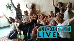 15 unga kvinnor som vinkar till kameran.
