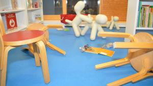 Omkullfallna stolar och skräp på golvet i Ingås bibliotek.