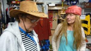 Maggi Ahlfors med stetsonhatt, Tiina Grönroos med röd pillerburk/hatt på huvudet