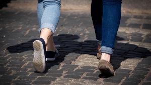 Kahden nuoren naisen jalat.
