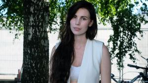 Den svenska artisten Skott poserar bakom scenen på årets Flow-festival (2017), hon är klädd helt i vitt och har långt, mörkt hår.