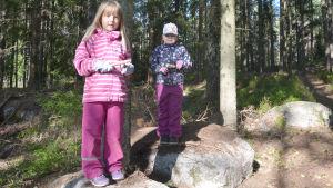Två flickor står på varsin sten och täljer.