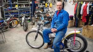 Harry Lahti sitter på en speedwaymotorcykel i sitt garage.