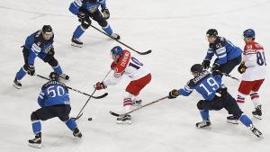 Roman Cervenka från Tjeckien omgiven av finska landslagsspelare i en ishockeymatch.
