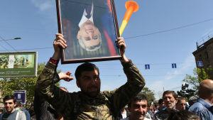 Demonstrant håller ett porträtt av premiärminister Serzj Sargsian upp och ner under en av de många demonstrationerna i huvudstaden Jerevan.