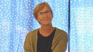 Barnträdgårdslärare Heidi Kihlstedt framför en gardin på Solbacka daghem.