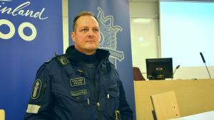 överkonstapel jukka sillanpää har uniform på sig och står med en bakgrund av en polisbanderoll.