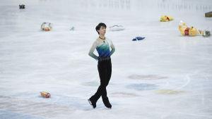 Konståkaren Yuzuru Hanyu står på isen som täcks av nallar och blommor.