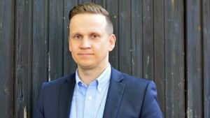 Personporträtt av kriminalkommissarie Mats Sjöholm. Han står vid en mörk dörr i klädd en mörkblå kostym.
