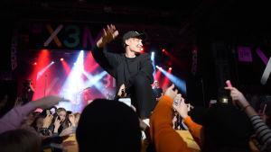 Isac Elliot står på scenen. I förgrunden syns publikens händer.