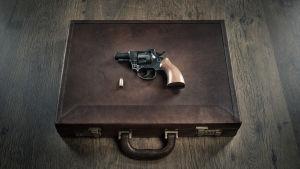 En revolver ligger på en liten kappsäck.