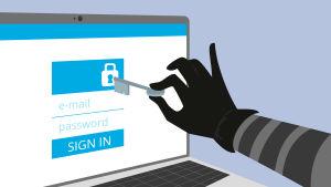 En hand som håller i en nyckel sträcker sig mot en dataskärm som visar ett lås och inloggning till ett e-postkonto.