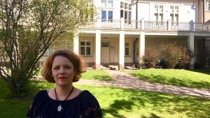 En kvinna står framför ett hus.