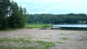 Badstrand vid havsvik med brygga och träd intill. Vass ute i vattnet och på andra sidan syns båtar, hus och träd.