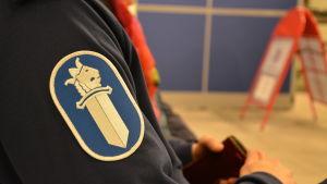 Närbild på polisens vapensymbol på en polismans ärm.