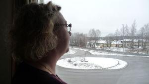 kvinna som tittar ut genom fönster. man ser knappt ansiktet.
