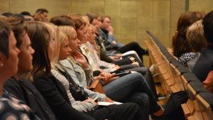 Abiturienter sitter på rad och lyssnar på en föreläsare.
