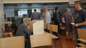 Fullmäktigeledamöter skriver namnet på röstsedlar i stadsdirektörsvalet i Lovisa