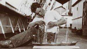 Den åländske sjömannen Runar Husell på ett däck sittandes vis ett modellfartyg.
