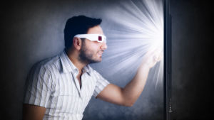 En man med 3D-glasögon sätter pekfingret mot en tv-skärm.