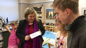 Språkbolärarinnan Katarina Norling håller upp en skylt där det står bada åt eleverna i hennes estlandssvenska grupp.