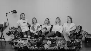 Fem kvinnor sitter i en blommig soffa. De har på sig jeans och vita t-sjortor. De ler och ser glada ut.