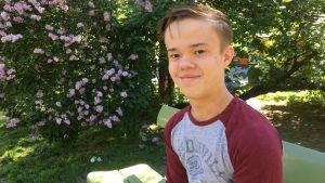 Henrik Krogius sitter på en parkbänk med syrenbuskar i bakgrunden.