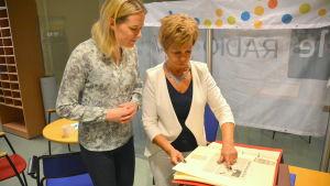 Katarina Lind och Gia Mellin-Kranck tittar på gamla tidningsurklipp.