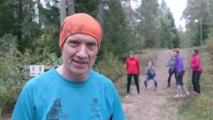 Evert Nilsson sysslar med CrossNature i en skog i Pargas, i bakgrunden andra deltagare