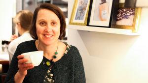 En person (Annika Sandelin) håller i en kaffekopp och ler.