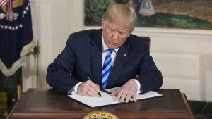 Trump skriver under dokument gällande att dra sig ur Iranavtalet.