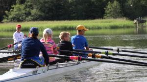 Barn som ror en tävlingsroddbåt.