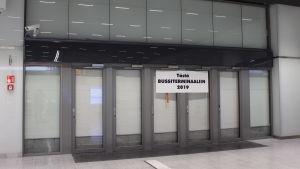 En skylt där det står att bussterminalen ska öppna 2019 på tillbommade dörrar