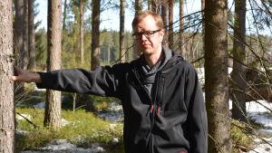 Biolog och naturföretagaren Mattias Kanckos lutar sig mot en tall i en gles skog. Vårsolen skiner och det finns en del snöfläckar ovanpå lingonriset i bakgrunden.