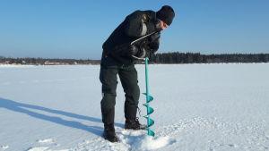 Sjöbevakningsmästare Michael Nordlund testar isens tjocklek utanför Vallgrunds sjöbevakningsstation.