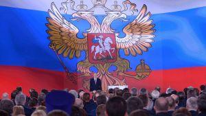 Vladimir Putin framför en enorm rysk flagga, då han höll sitt årliga linjetal den 1 mars 2018.