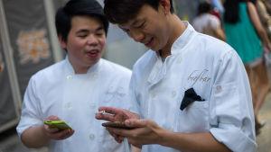 Två män i Hong Kong står och spelar på sina telefoner under en arbetspaus.