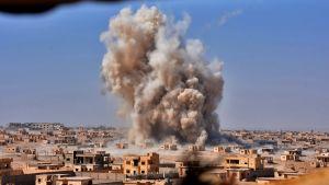 Rök stiger från den syriska staden Dayr az-Zawr, som belägrats av IS sedan 2014.