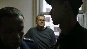Rysslands tidigare ekonomiminister Aleksej Uljukajev står och väntar mellan två poliser.