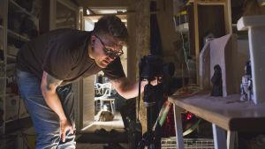 Janne Mällinen tittar in i kameran och fotograferar miniatyrer.