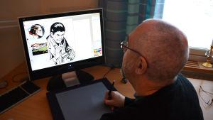 Äldre man sitter framför dator