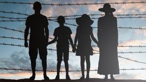 Silhuett av familj vid stängsel av taggtråd.