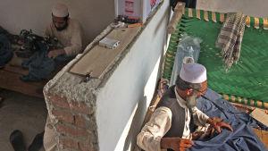Tvä afghanska män jobbar sitter och syr kläder