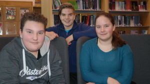 Ungdomarna Joacim Oksanen, Viggo Henelius och Olivia Numminen i biblioteket i Kimito