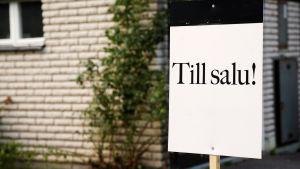 Till salu-skylt utanför ett vitt tegelhus.