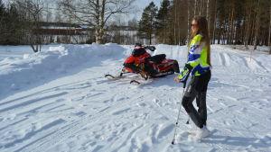Carolina Wärn står brevid på en snöskoter hemma i Esse.