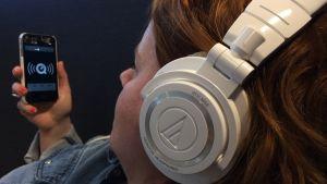 Nainen kuuntelee kännykästä podcastia.