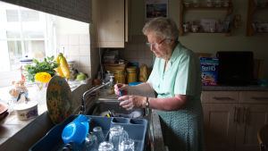 En pensionär som bor ensam står vid dsikhon i sitt kök.