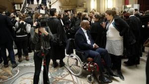 Bley Bilal Mokono sitter i en rullstol omringad av många människor.