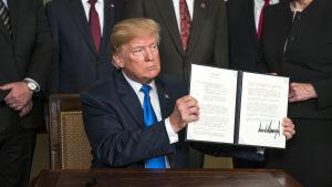 USA:s president Donald Trump visar upp ett undertecknat beslut